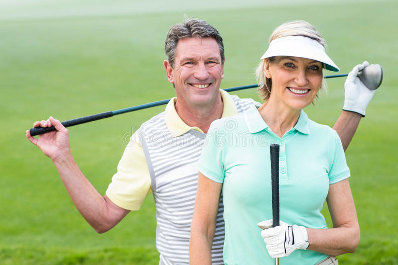微笑对照相机的打高尔夫球的夫妇拿着俱乐部 免版税库存照片