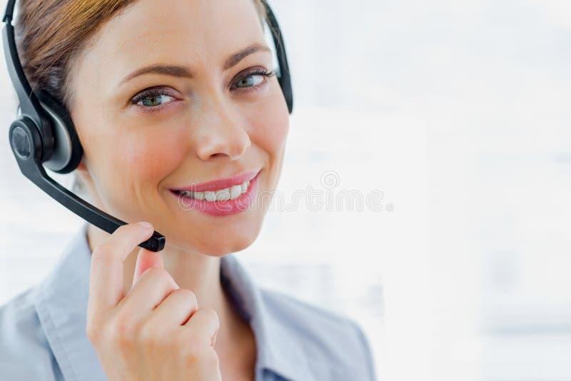 微笑对照相机的电话中心操作员佩带的耳机 图库摄影
