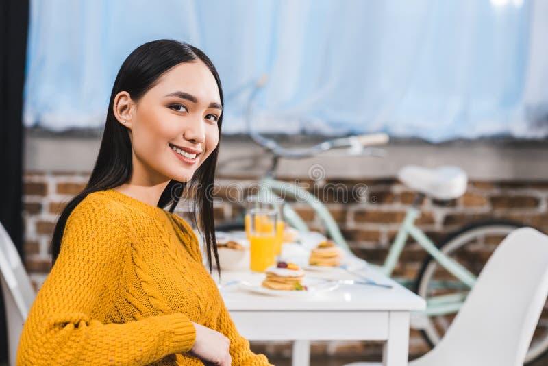 微笑对照相机的美丽的年轻亚裔妇女,当坐时 免版税库存照片