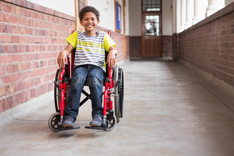 微笑对照相机的逗人喜爱的残疾学生在大厅里 库存照片