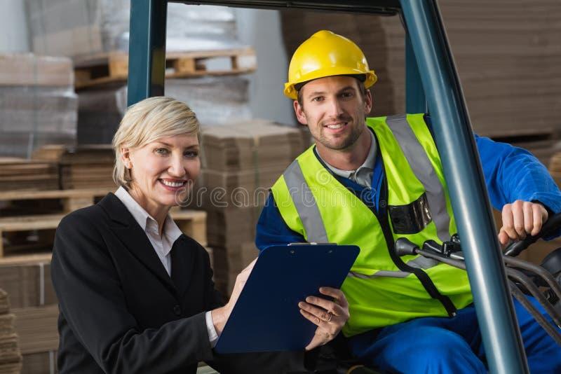 微笑对照相机的铲车司机和经理 库存照片