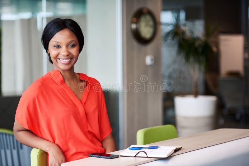 微笑对照相机的黑人企业家,当在家时坐 库存图片