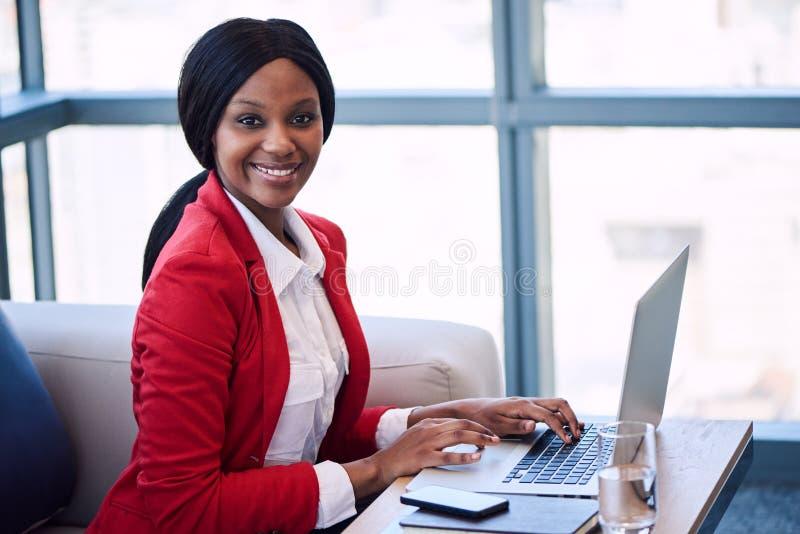 微笑对照相机的黑人女实业家,当安装在沙发时 库存图片