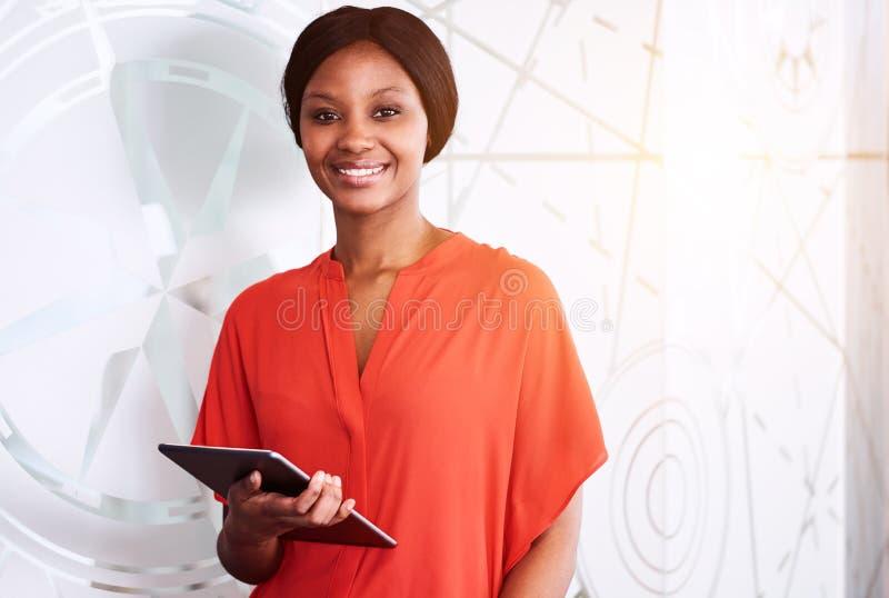 微笑对照相机的黑人女实业家,当拿着电子片剂时 库存图片
