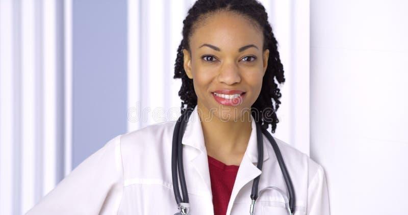 微笑对照相机的黑人妇女医生 库存图片