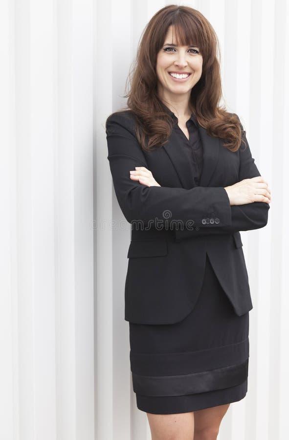 微笑对照相机的活跃女实业家 免版税库存图片