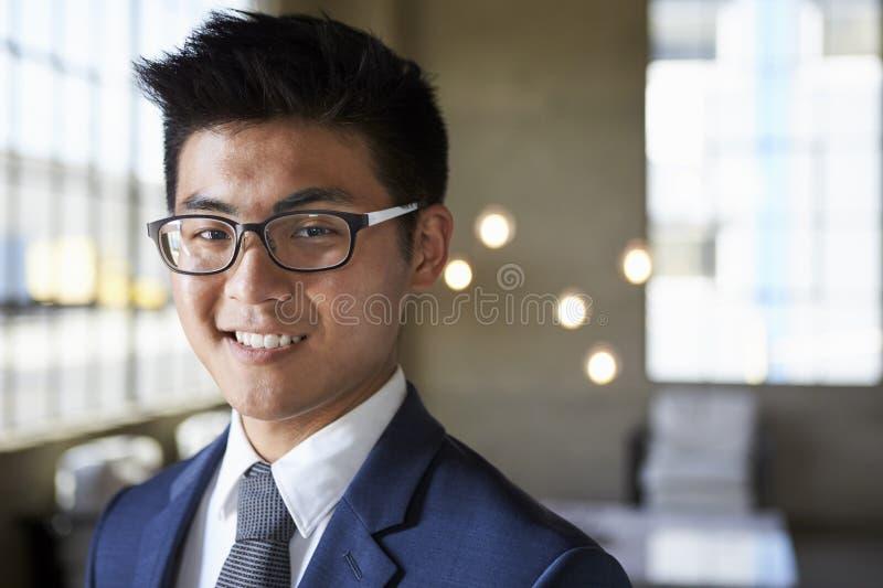 微笑对照相机,首肩的年轻亚洲商人 免版税图库摄影