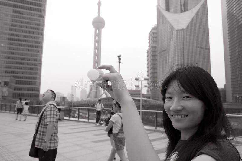 微笑对珍珠塔的亚裔妇女 图库摄影
