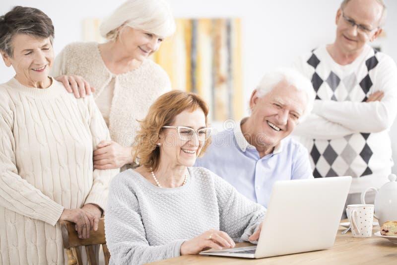 微笑对膝上型计算机的长辈 库存照片