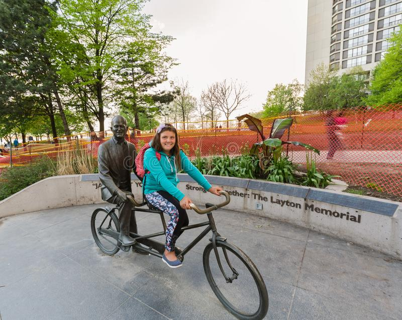 微笑小女孩坐有一个人雕象的一辆自行车在她后在多伦多进城区域 免版税库存图片