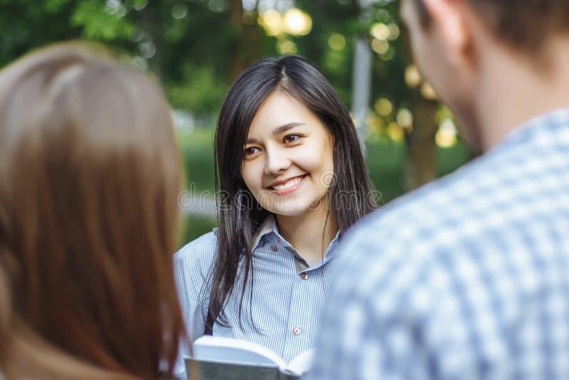 微笑小组的青年人谈话和户外 免版税库存图片