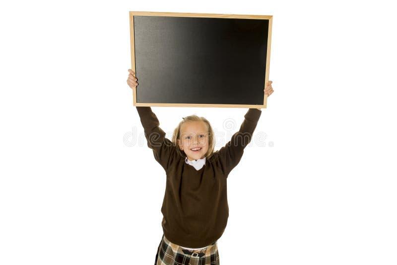 微笑小美丽的白肤金发的女小学生愉快和快乐的藏品和陈列小空白的黑板 库存图片
