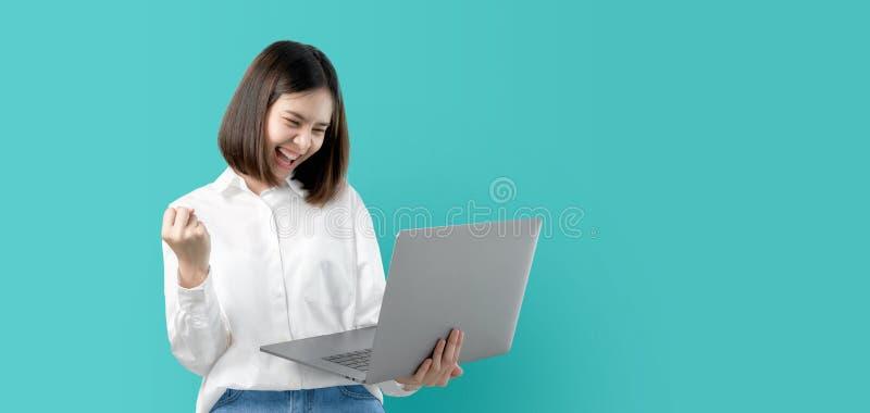 微笑年轻亚裔的妇女拿着手提电脑用拳头手和激发为在浅兰的背景的成功 免版税图库摄影