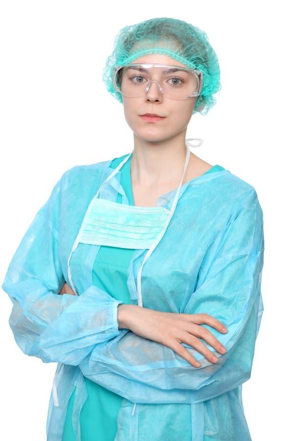 微笑年轻女性外科医生的医生站立与横渡的胳膊和,隔绝在白色背景 库存照片