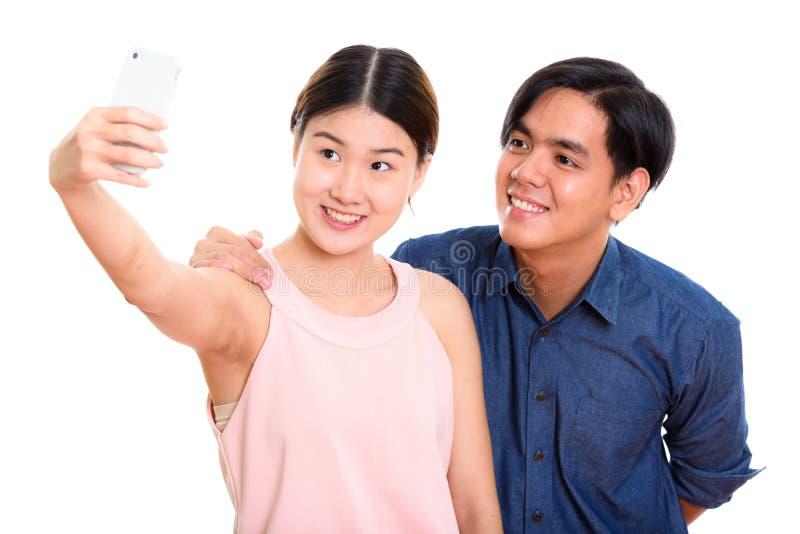 微笑年轻愉快的亚洲的夫妇,当采取selfie图片机智时 免版税图库摄影