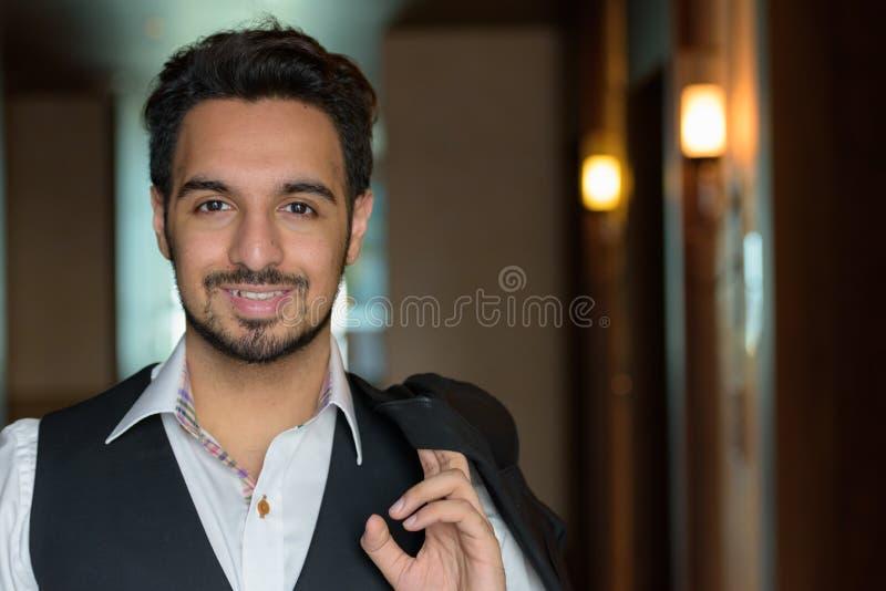 微笑年轻愉快的印度的人,当拿着在corri时的夹克 免版税库存照片
