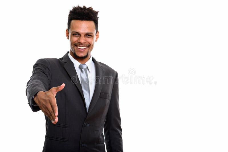微笑年轻愉快的非洲的商人,当给握手时 免版税库存照片