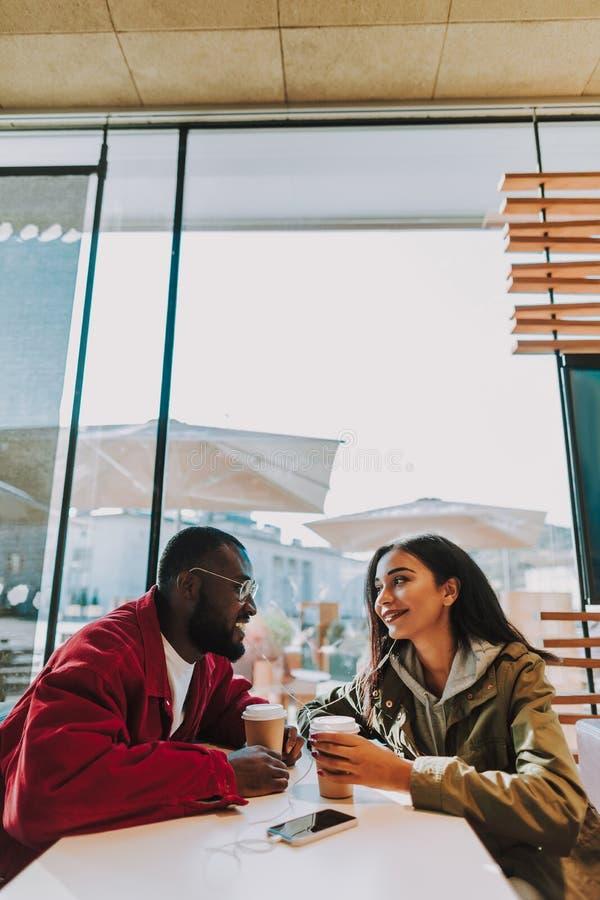 微笑年轻的夫妇正面照片,当在咖啡馆时 免版税库存图片