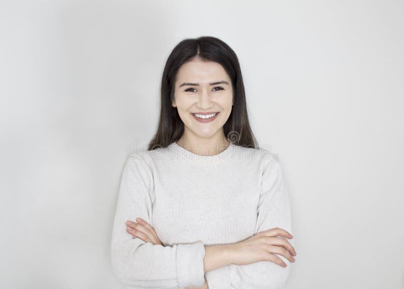 微笑年轻美丽的逗人喜爱的快乐的女孩画象看在白色背景的照相机 免版税库存照片