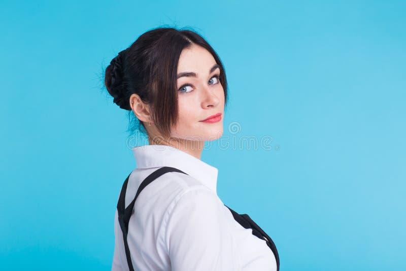 微笑年轻美丽的逗人喜爱的快乐的学生的女孩画象看在蓝色背景的照相机 库存图片