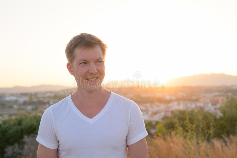 微笑年轻英俊的旅游的人,当认为在小山顶部时 免版税库存照片