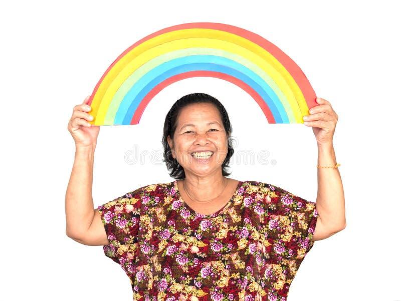 微笑年长亚裔的妇女,当拿着五颜六色的彩虹o时 库存照片