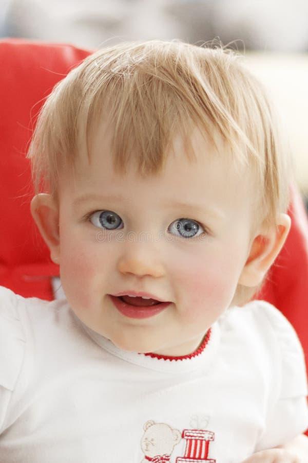 微笑并且看照相机一个小女孩的画象有蓝眼睛的 免版税库存照片
