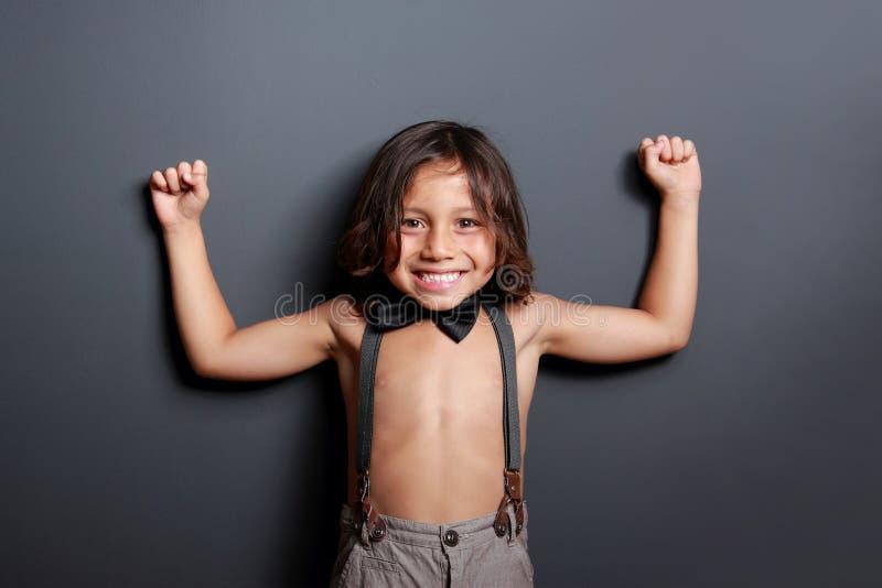 微笑快乐的逗人喜爱的小男孩摆在和 免版税库存图片