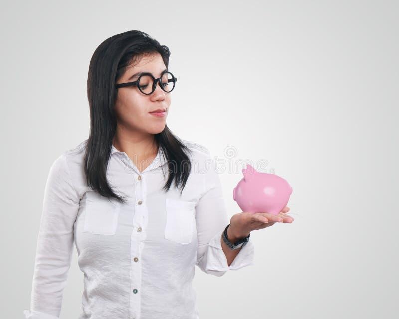微笑愉快的亚裔的女实业家,当看起来在她的手上时的存钱罐 免版税图库摄影