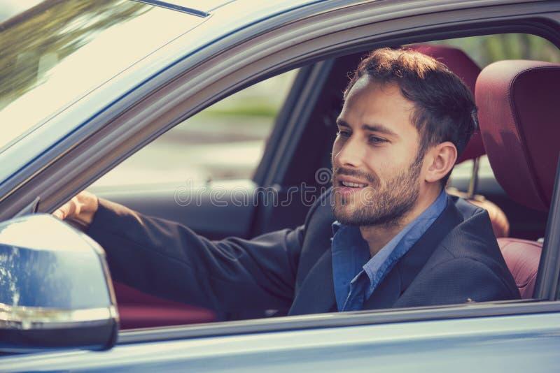 微笑愉快的人的司机驾驶看在旁边镜子的体育蓝色汽车 免版税库存照片