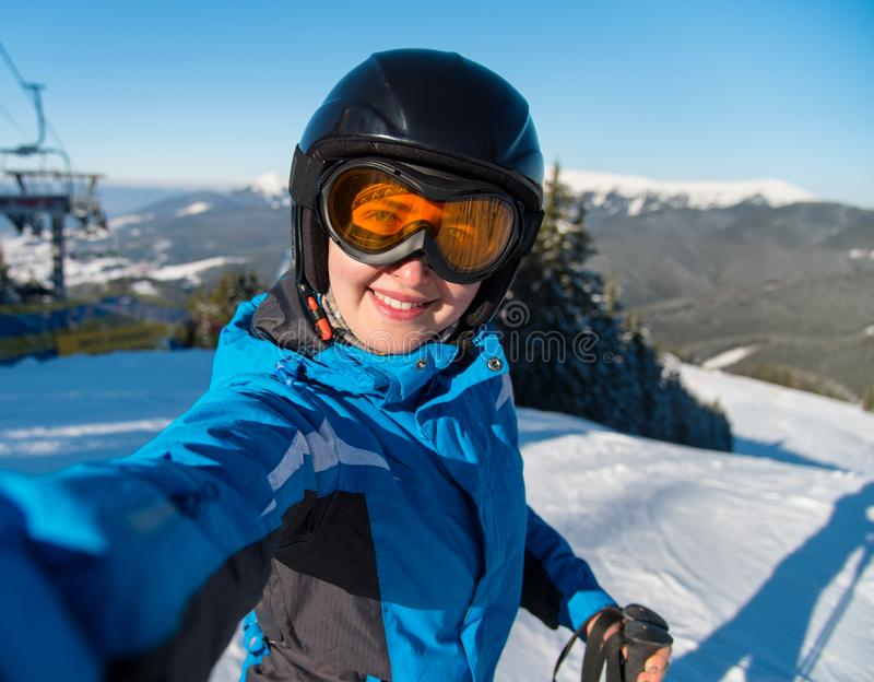 微笑愉快的女子的滑雪者特写镜头画象,采取selfie,当基于倾斜时在滑雪以后 免版税库存照片