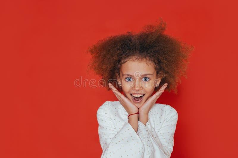 微笑愉快的女孩特写画象有卷发的看照相机 免版税库存图片