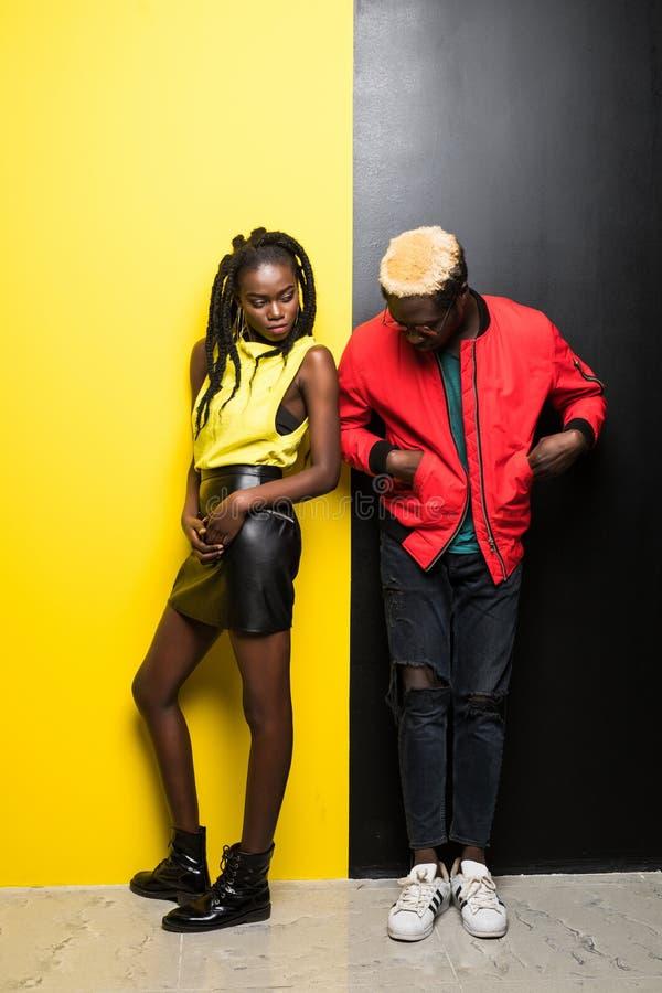 微笑愉快的嫩年轻的夫妇和获得在五颜六色的背景的乐趣 美国黑人的在黄色和黑色隔绝的男人和妇女 图库摄影