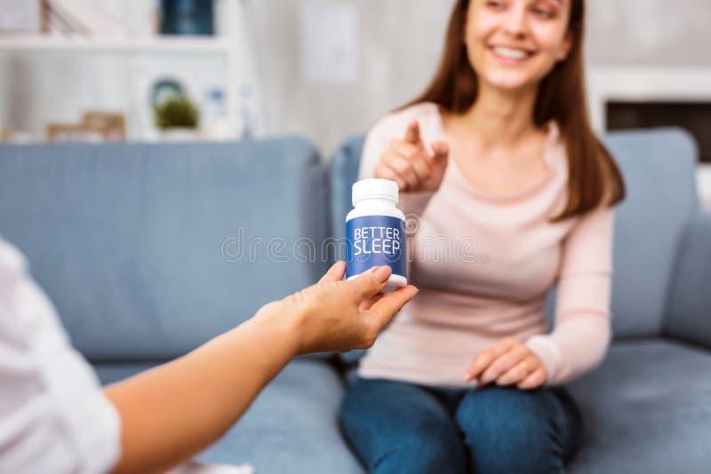 微笑愉快的患者,当看药片为更好的睡眠时 免版税库存照片