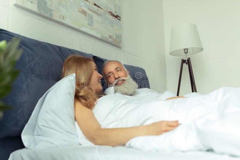 微笑愉快的成熟的夫妇一起在床上和 库存照片