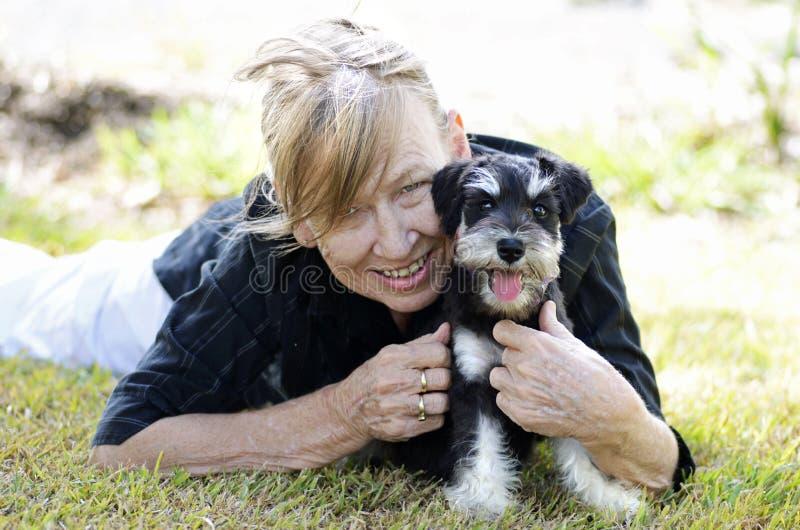 微笑愉快的成熟资深的妇女拥抱宠物小狗 免版税库存图片