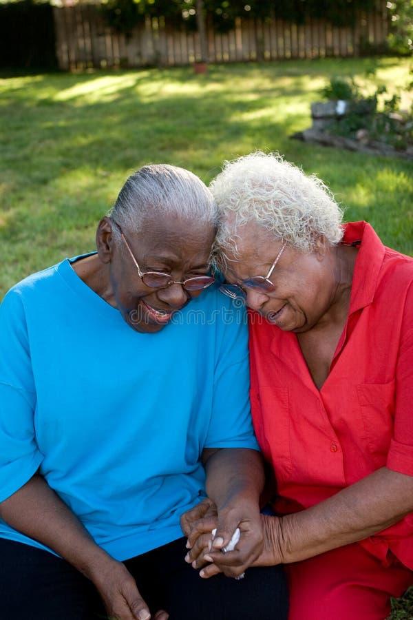 微笑愉快的成熟非裔美国人的姐妹笑和 图库摄影