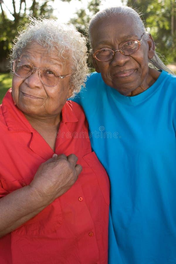 微笑愉快的成熟非裔美国人的姐妹笑和 免版税库存图片