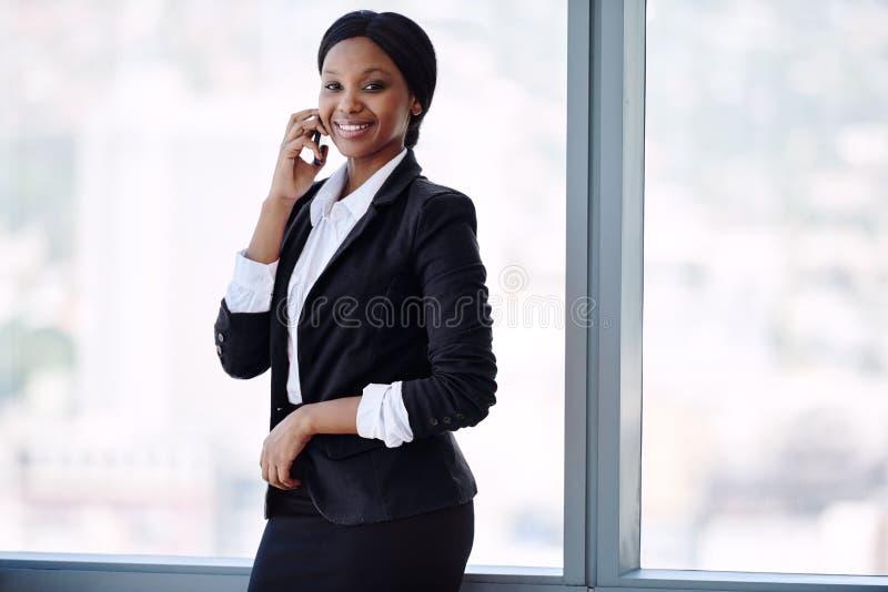 微笑愉快的非洲的女实业家,当谈话在她的手机时 库存图片