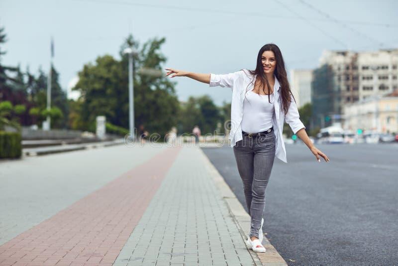 微笑户外在城市街道上的美丽的愉快的深色的妇女 免版税库存照片