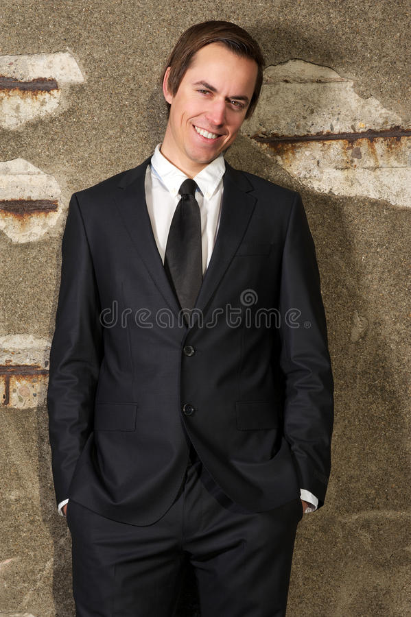 微笑户外在轻松的姿势的愉快的商人 库存图片