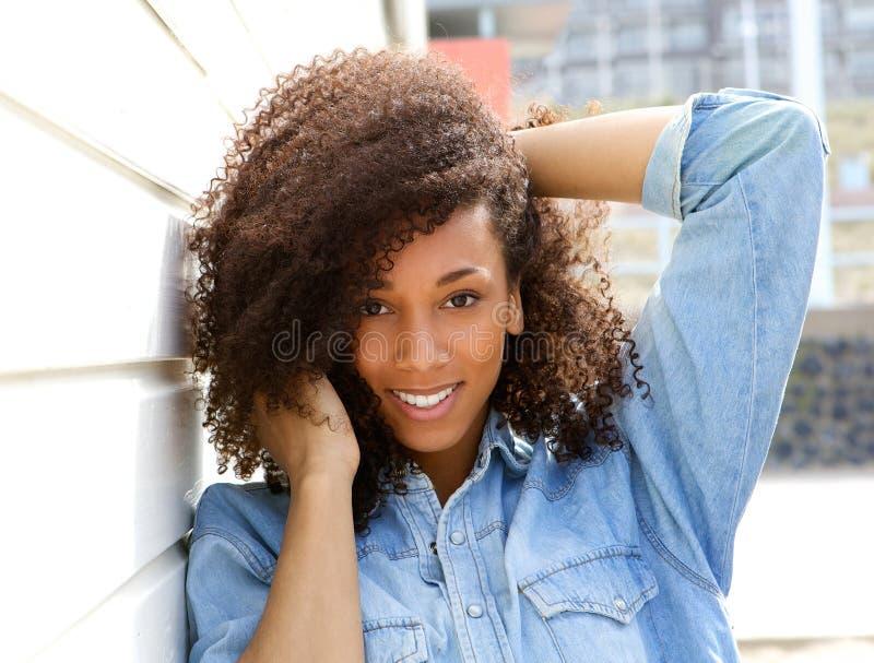 微笑户外用在头发的手的非裔美国人的妇女 免版税库存照片