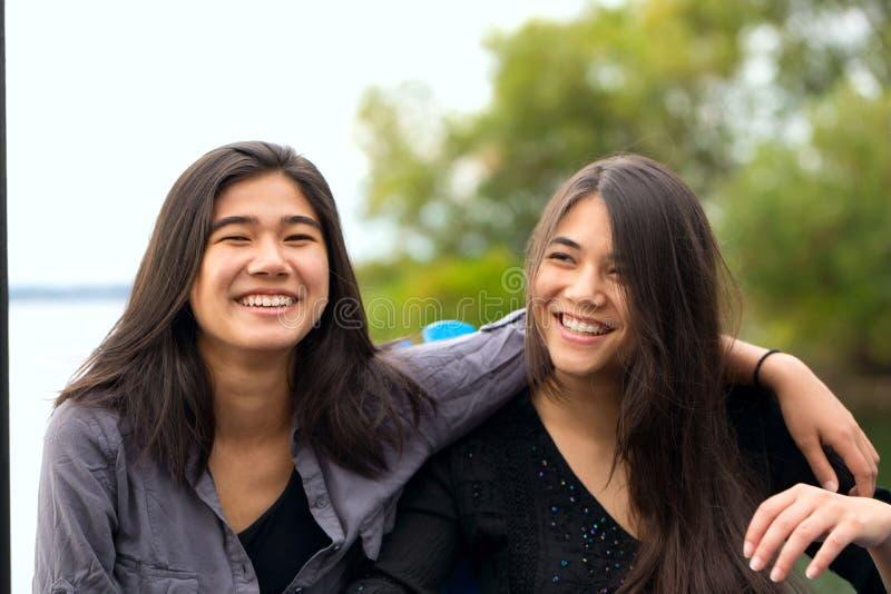 微笑户外由湖,huggi的两个微笑的两种人种的青少年的女孩 图库摄影