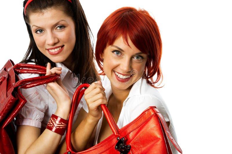微笑手袋的红色二名妇女 免版税库存照片