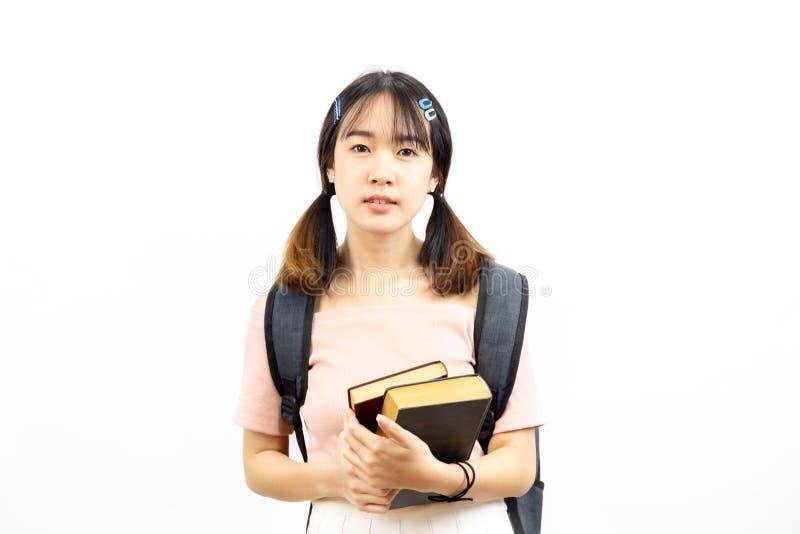 微笑拿着堆与袋子的书的愉快和偶然亚裔女性大学生 免版税库存图片