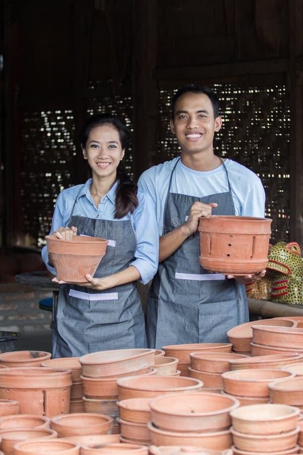 微笑拿着他们的在瓦器的男性和女性陶瓷工产品 图库摄影