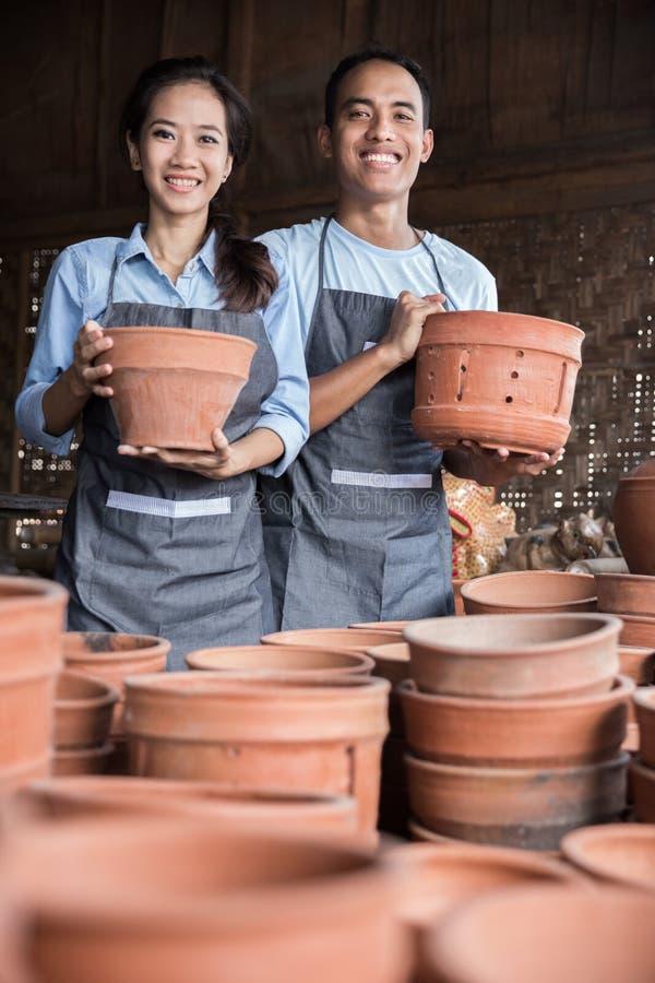 微笑拿着他们的在瓦器的男性和女性陶瓷工产品 免版税图库摄影