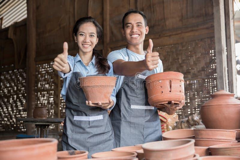 微笑拿着他们的在瓦器的男性和女性陶瓷工产品 免版税库存图片