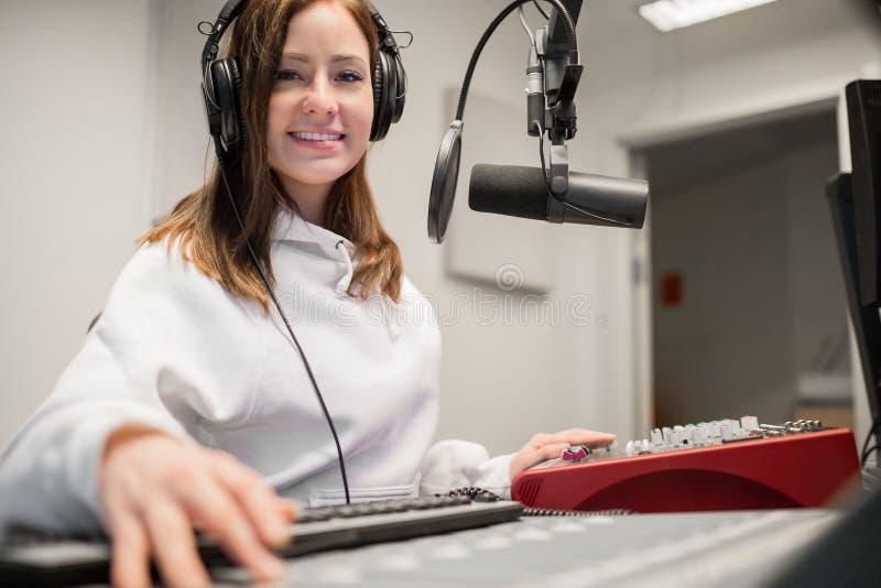 微笑无线电的骑师,当佩带耳机在演播室时 免版税库存图片