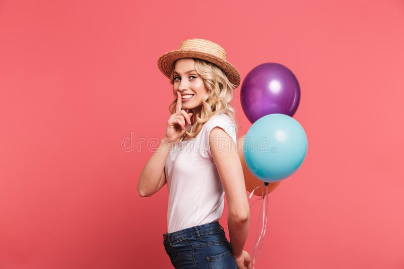 微笑时髦白肤金发的妇女20s佩带的草帽画象,当拿着束五颜六色的气球时 库存图片